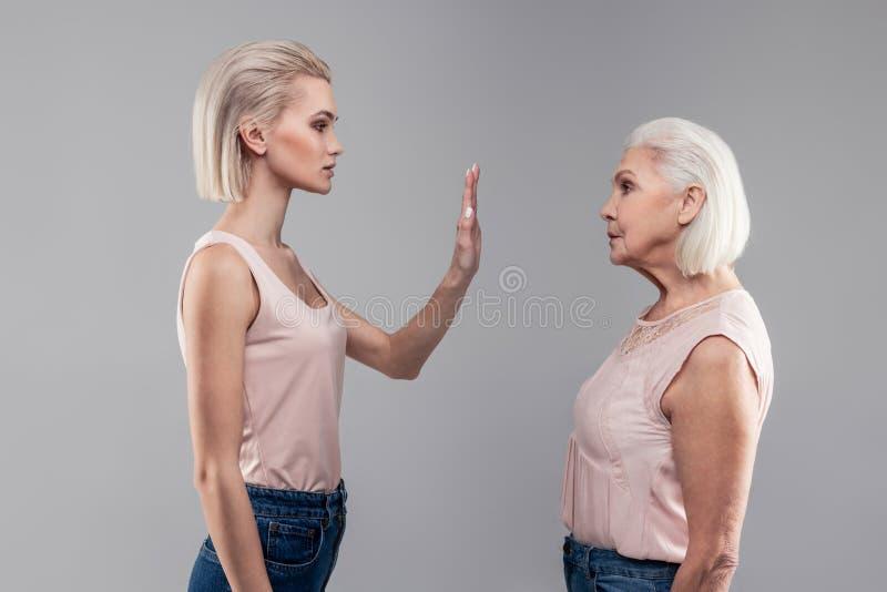 显示她的棕榈的短发白肤金发的年轻女人对前辈 免版税库存图片