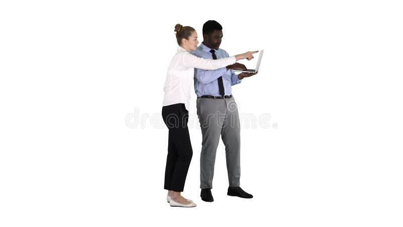 显示某事在膝上型计算机屏幕上的美国黑人的企业顾问谈话与白色背景的白女实业家 库存图片