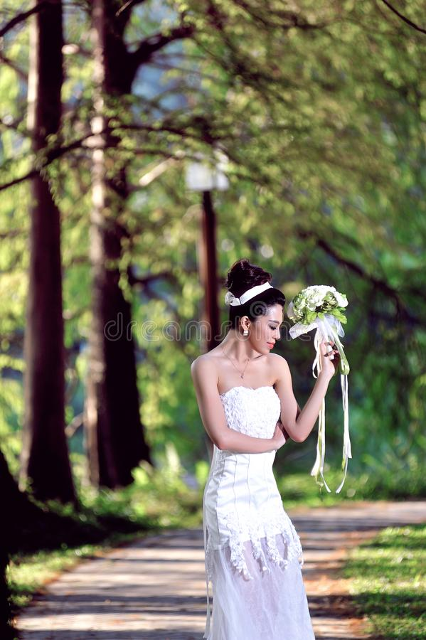 显示愉快的片刻的婚纱的美丽的亚裔女孩 图库摄影