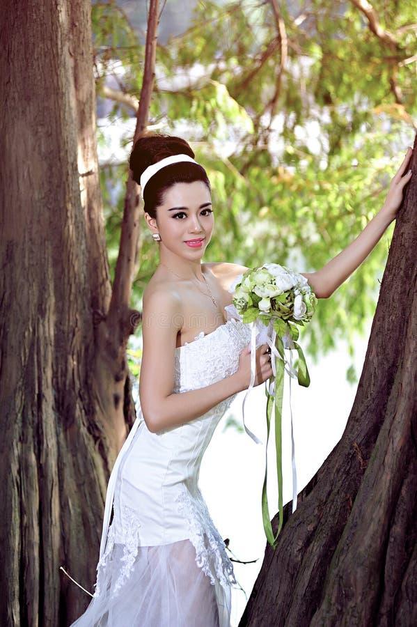 显示愉快的片刻的婚纱的美丽的亚裔女孩 免版税库存图片