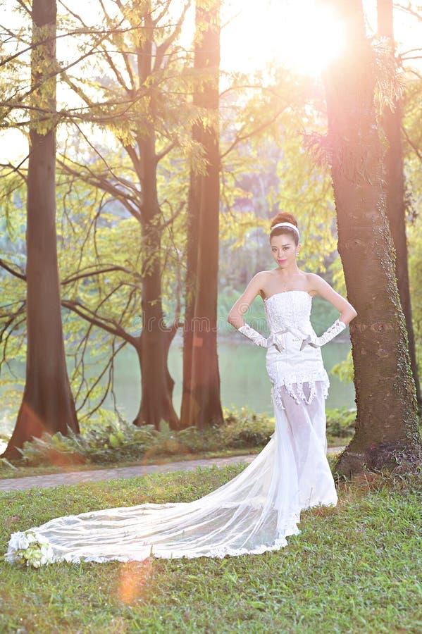 显示愉快的片刻的婚纱的美丽的亚裔女孩 免版税库存照片