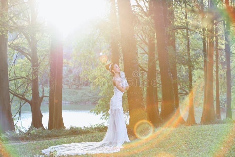 显示愉快的片刻的婚纱的美丽的亚裔女孩 库存图片