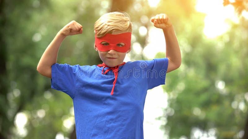 显示肌肉,作为精神疗法的比赛的超级英雄男孩儿童信心的 免版税库存照片