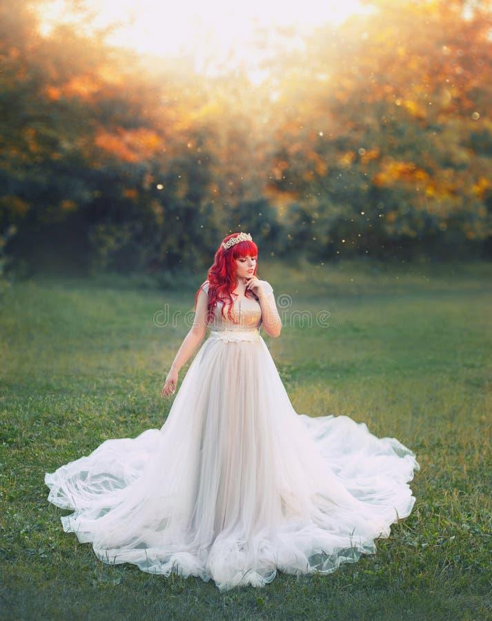 明亮的艺术照片,有红色头发的逗人喜爱的大肥满嫩女孩在有白色火车立场的长的银色轻的礼服 免版税库存图片