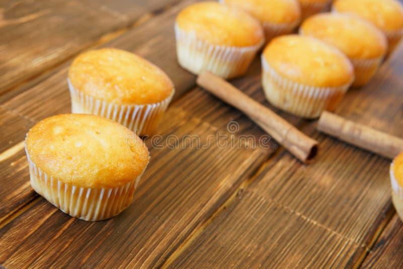 明亮的金黄杯形蛋糕和肉桂条说谎木表面上由杉木板做成 鲜美和健康食物 白天 库存照片