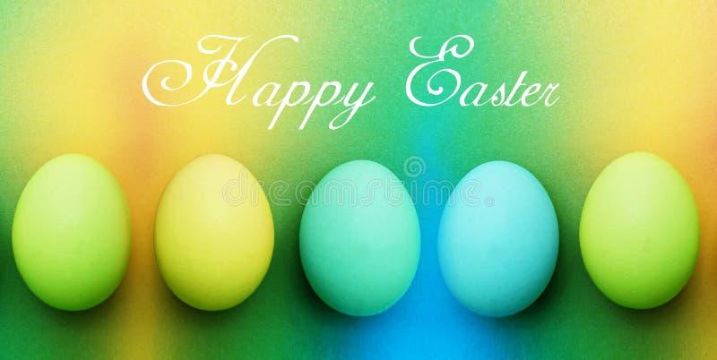 明信片用在彩虹背景的五个蓝色绿松石苹果绿的黄色复活节彩蛋 免版税库存照片