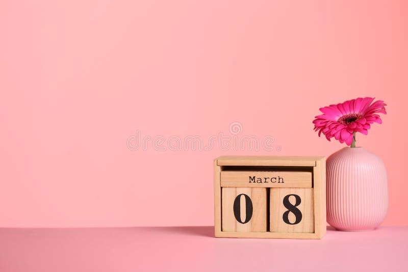 日历和花瓶有花的在桌上反对颜色背景,空间文本的 免版税库存照片