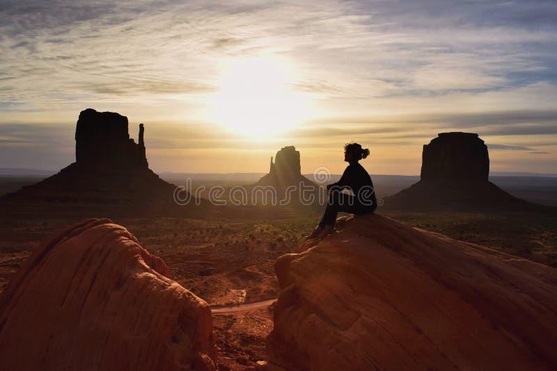 日出妇女徒步旅行者观看的吻合风景在纪念碑谷,犹他,美国的 库存照片