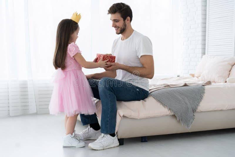 日父亲s 拥抱爸爸和笑的愉快的家庭女儿在度假 免版税库存图片