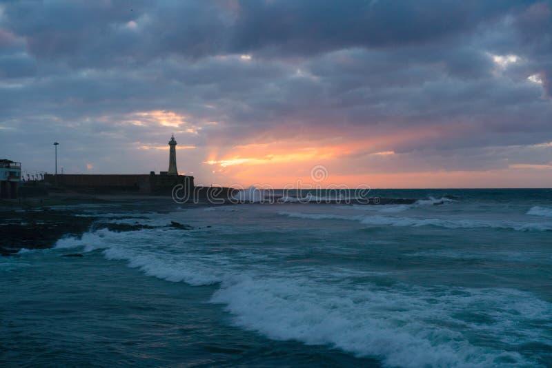 日落在大西洋的时间视图和灯塔在拉巴特,摩洛哥的首都 免版税库存照片