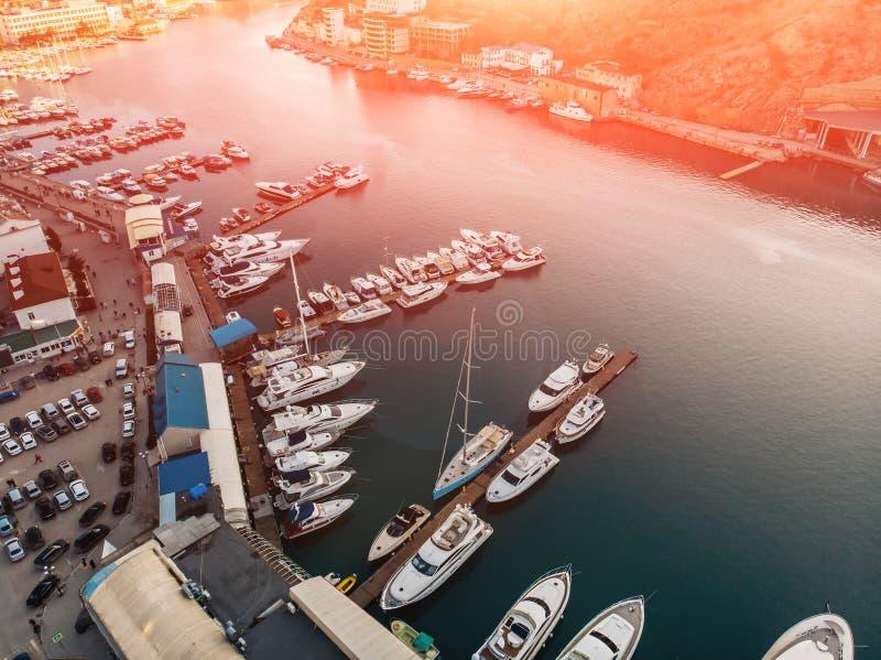 日落鸟瞰图在Balaklava,克里米亚与许多游艇和小船的海的海湾在山之间的手段海岸 免版税库存图片