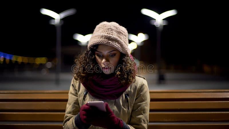 旧男友吃惊的女孩观看的照片有新的女朋友的,使用电话 免版税库存照片