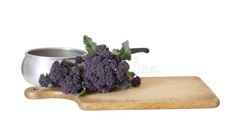 早期的紫色洋椰菜花春天菜,与葡萄酒平底深锅和木食物切板 查出在白色 免版税库存照片