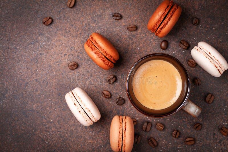 早晨在棕色台式视图的咖啡和点心macaron或蛋白杏仁饼干 免版税库存照片