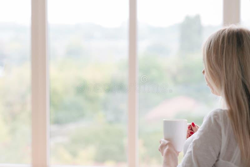 早晨饮料妇女神色窗口举行饮料 免版税库存图片