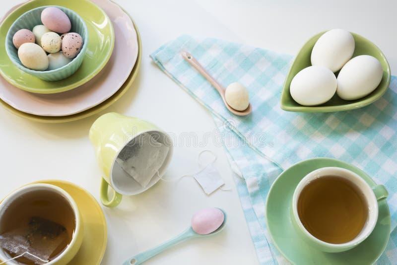 早餐用复活节彩蛋和茶在明亮的颜色 库存图片