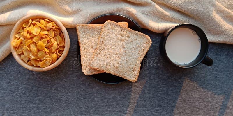 早餐:面包、谷物和牛奶在黑暗的背景 库存照片