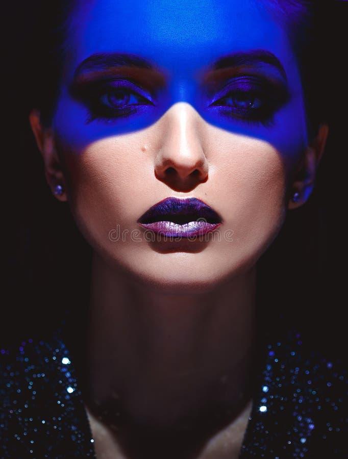 时尚女孩和在她的面孔的蓝色霓虹灯画象有时髦的构成的在黑背景在演播室 免版税库存照片