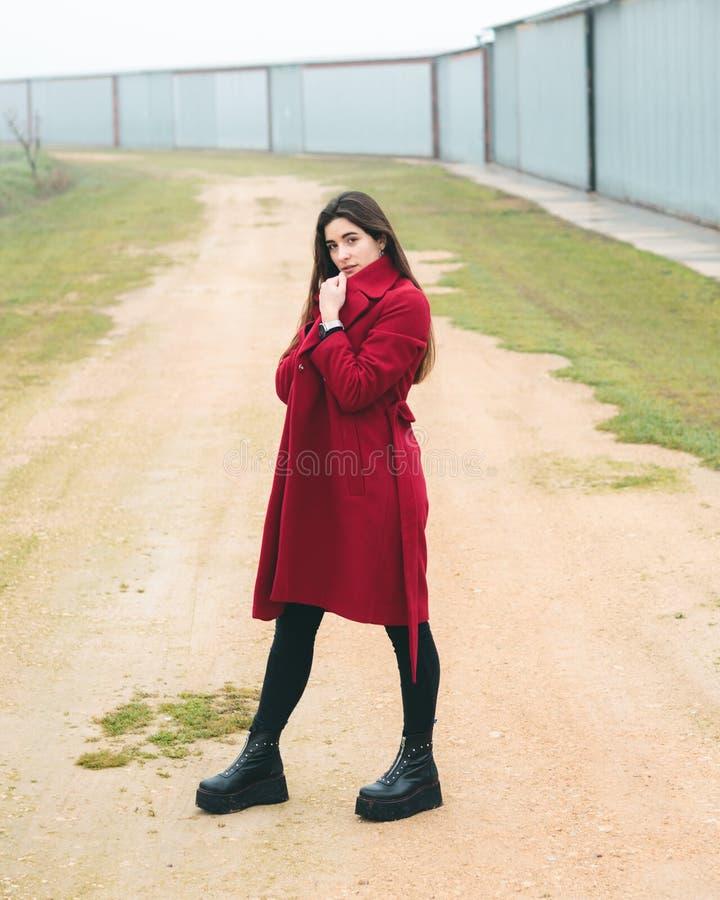 时尚摆在一个农村场面的年轻俏丽的女孩妇女画象在欧洲 冬天和春天时尚,穿一件红色夹克 图库摄影