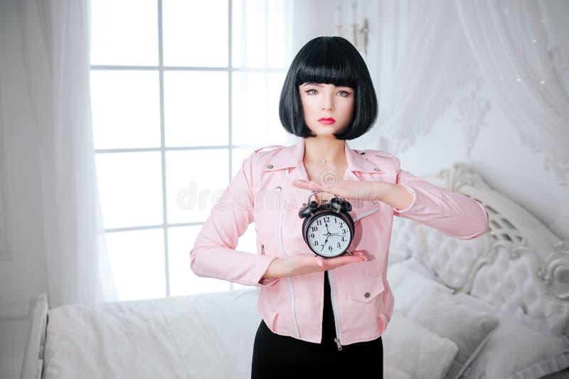 时尚畸形人 魅力综合性女孩、假玩偶有空的神色的和短的黑色头发拿着时钟,当站立时 图库摄影