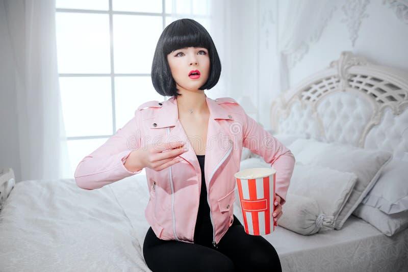 时尚畸形人 魅力综合性感兴趣的女孩,有短的黑色头发的假玩偶拿着玉米花并且看电视 免版税图库摄影