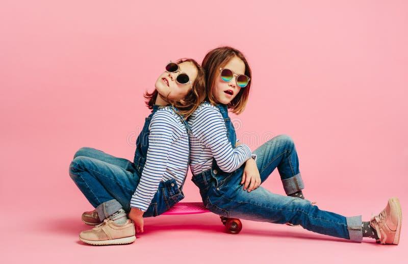时尚衣裳的时髦的逗人喜爱的女孩在滑板 免版税图库摄影
