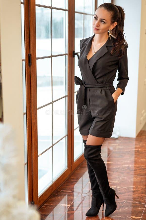 时兴的女孩站立在窗口并且看起来时髦的衣裳 免版税图库摄影