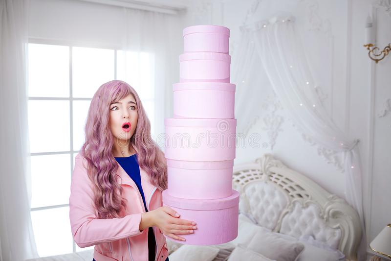 时兴的畸形人 有长的淡紫色头发的魅力情感美女拿着桃红色箱子,当站立在白色时 免版税库存图片