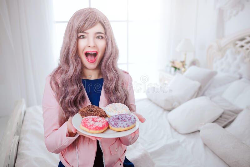 时兴的畸形人 魅力愉快的美女画象有长的淡紫色头发的拿着在板材的五颜六色的多福饼 免版税库存照片