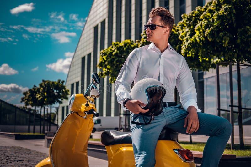 时髦的坐滑行车和看斜向一边在街道的人佩带的太阳镜在一好日子 库存照片