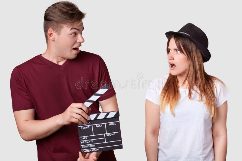 时髦的头饰看看的恼怒的妇女举行clapperboard,冲击了表示,建议新的场面,被聚焦的她的生产商 免版税图库摄影