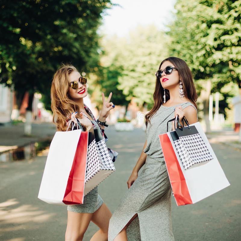 时髦的女孩夫妇在购物的与购物带来以后 库存图片