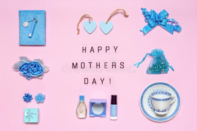 时髦的女性辅助部件,花,化妆用品,香水,在蓝色淡色的礼物在桃红色背景 文本愉快的母亲节 免版税库存照片