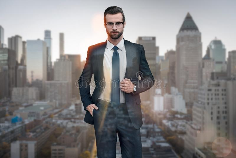 时髦的生意人 看照相机的衣服的英俊的年轻人保留一只手在口袋,当站立反对时 库存照片