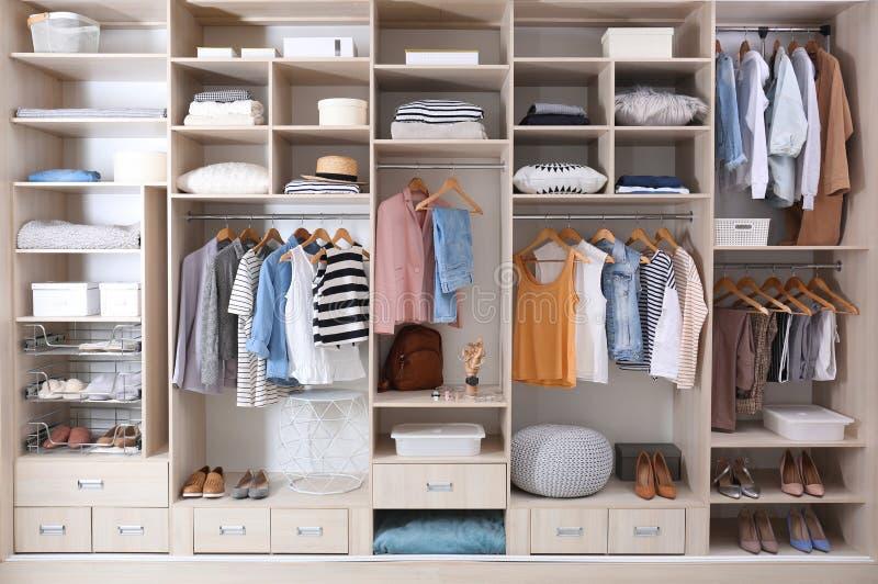 时髦的衣裳、鞋子和家庭材料在大衣橱 免版税图库摄影