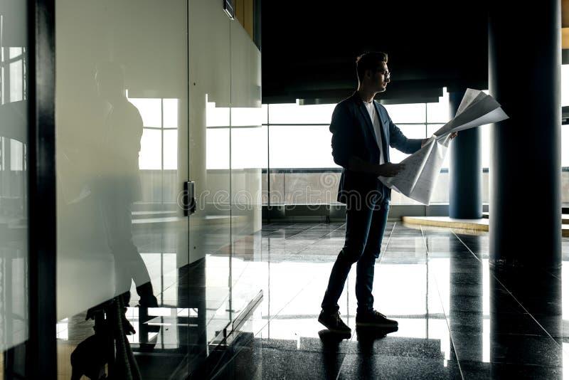 时髦的衣裳的建筑师由在一块现代玻璃的背景的电话拿着与图画的板料在他的手和谈话上 免版税库存图片