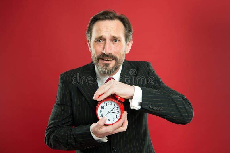 时间安排技能 多少时刻离开直到最后期限 有闹钟的经理 人有胡子的商人举行时钟 免版税库存图片