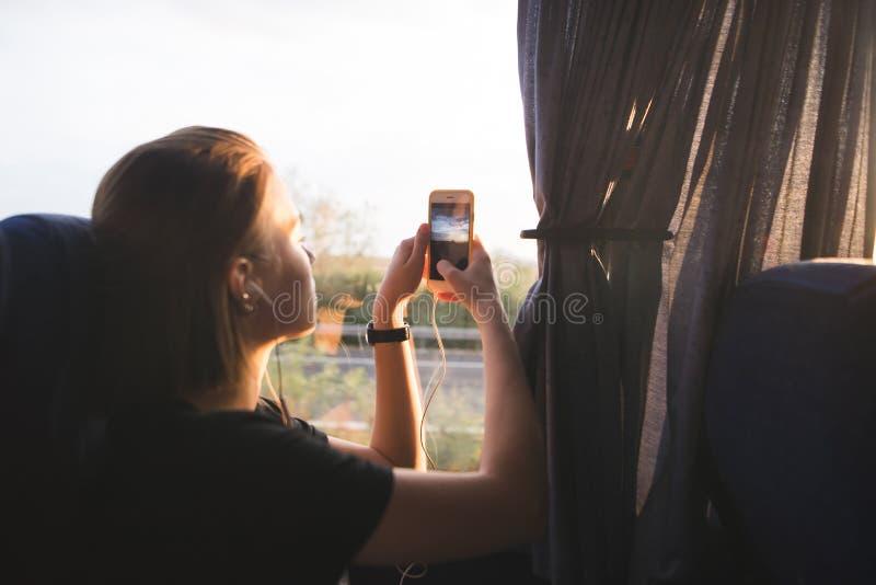 旅游妇女在公共汽车上在窗口和照片风景附近在日落坐智能手机 库存照片