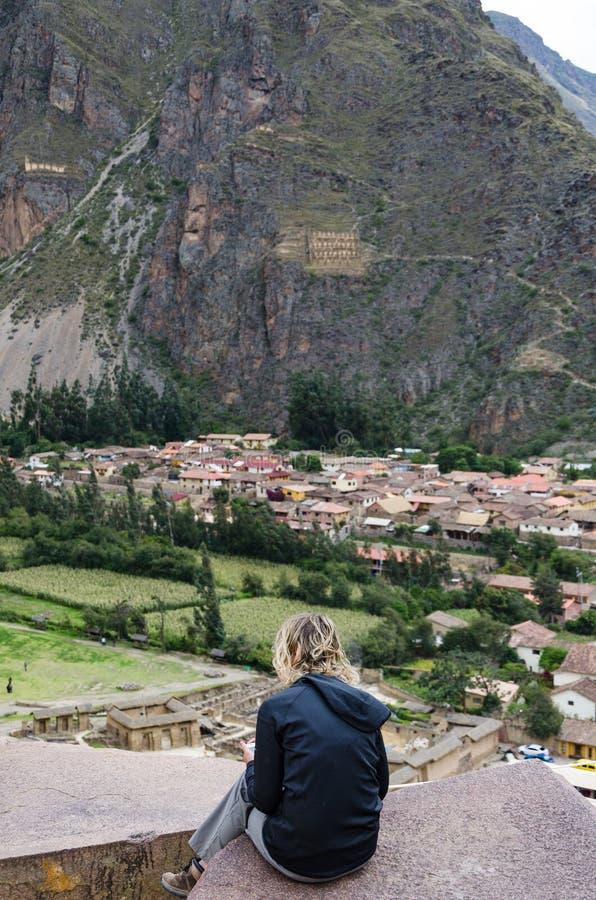 旅游摆在岩石在Ollantaytambo古老印加人堡垒的步顶部在神圣的谷的 库存图片