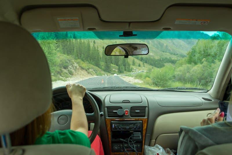 旅行乘在阿尔泰的山的汽车的两年轻美女由蜒蜒路驾驶 妇女神色对 库存图片