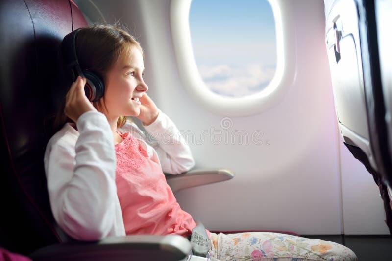 旅行乘飞机的可爱的少女 看的孩子坐由飞机窗口和外面,当听到音乐时 免版税库存图片