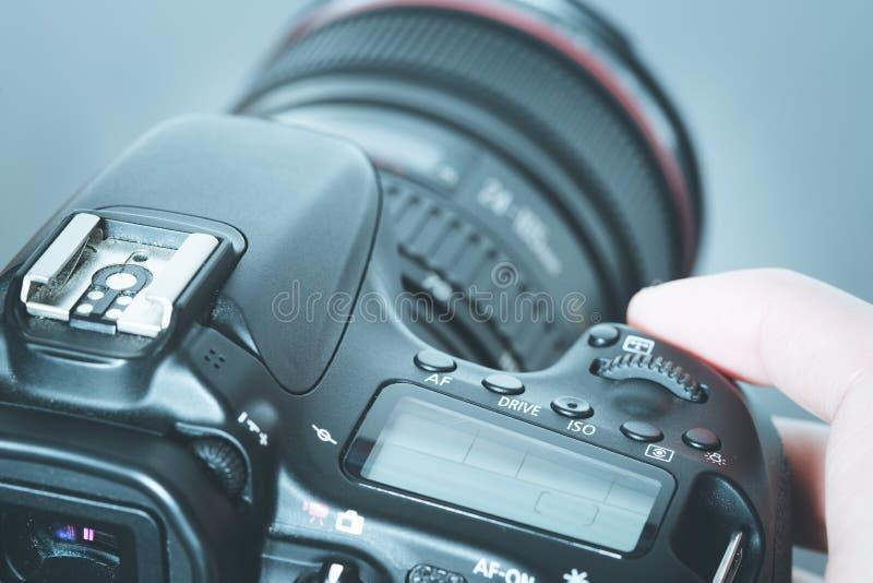 摄影师拿着与远摄镜头的一台反光照相机在他的手上 表和膝上型计算机在模糊的背景中 库存照片