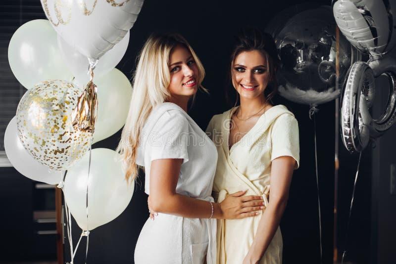摆在与女傧相的美丽的新娘在气球附近 库存图片