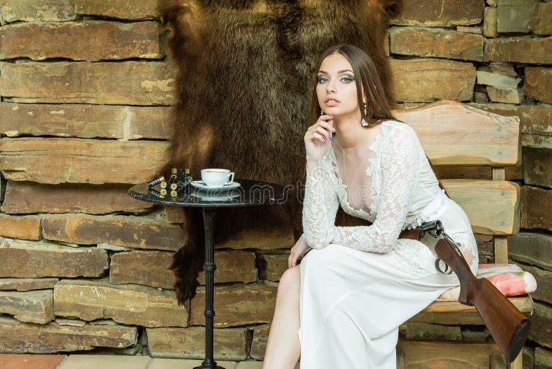 摆在与在熊皮肤的背景的一杆寻找的步枪的白色礼服的美女 免版税库存图片