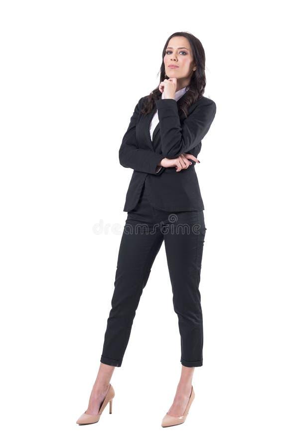 摆在与手指的衣服的典雅的美丽的白种人女商人在下巴下 免版税库存图片