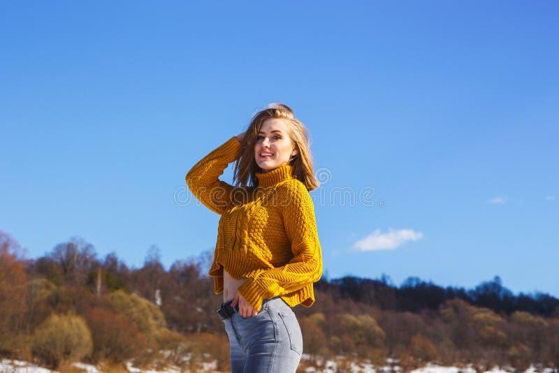 摆在反对天空蔚蓝和冬天森林的一件黄色毛线衣的女孩 免版税库存照片
