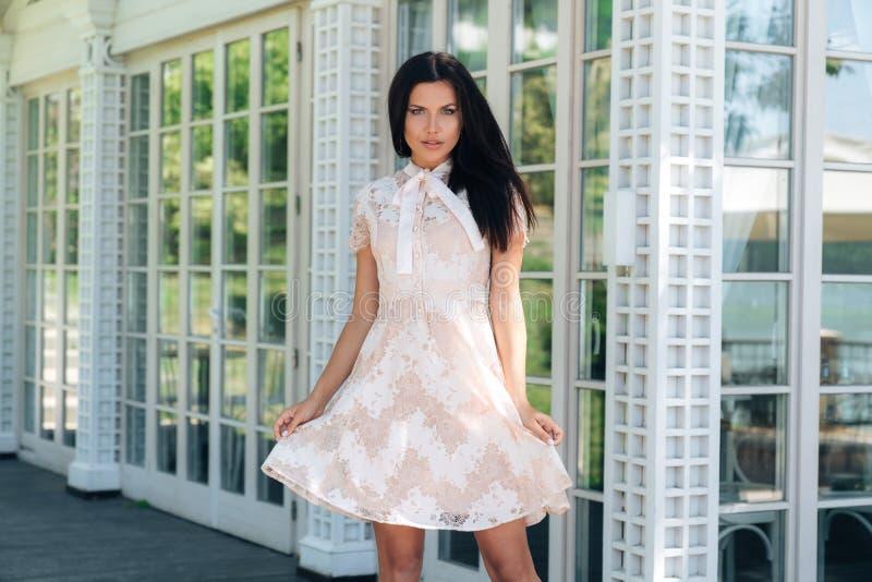 摆在在咖啡馆之外的米黄颜色礼服的美丽的深色的女孩在木和玻璃墙附近 免版税库存照片