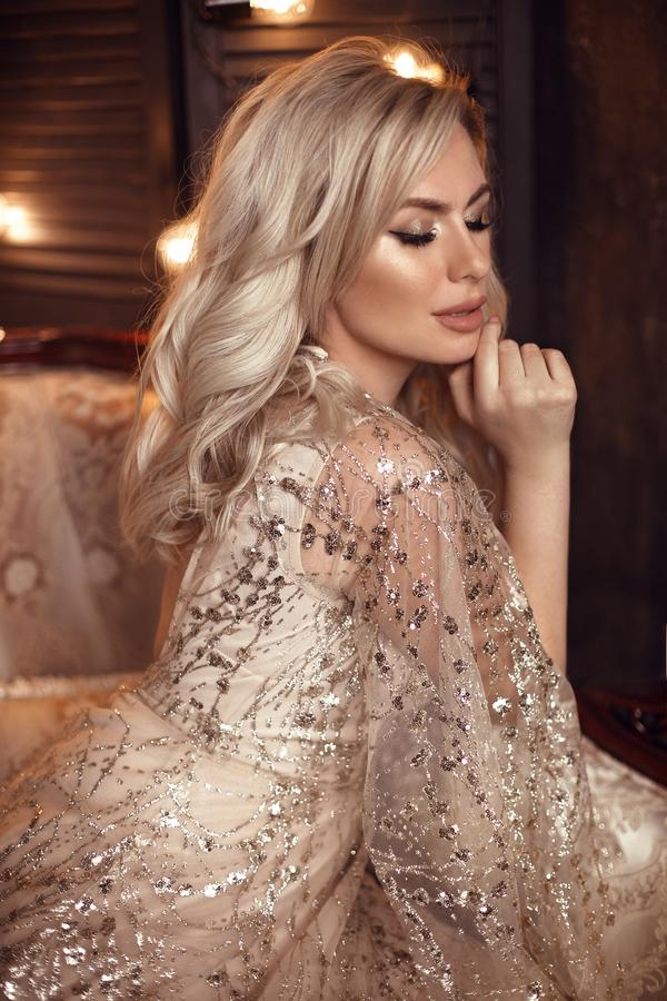 摆在在皇家内部的豪华沙发的米黄礼服的典雅的白肤金发的妇女 有构成的时尚美丽的肉欲的新娘,卷曲 免版税库存照片