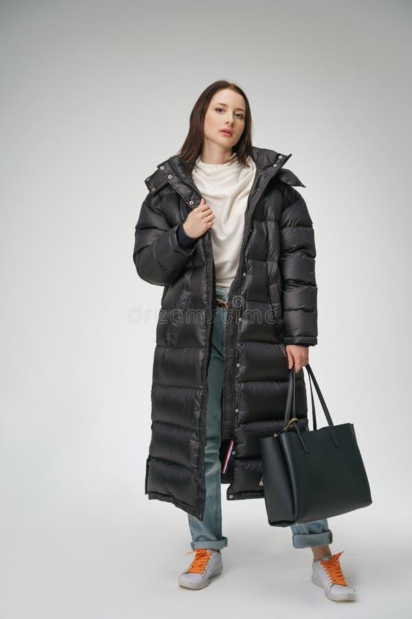 摆在在白色背景的一件长的冬天外套的年轻美女 免版税库存照片