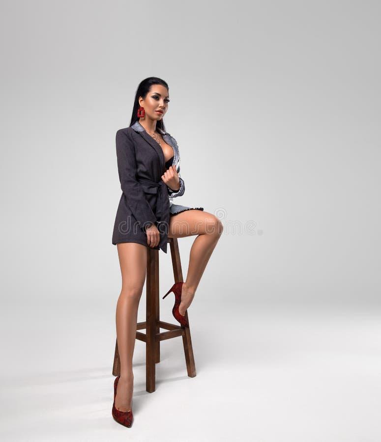 摆在椅子的性感的夹克的妇女 图库摄影